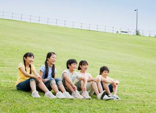 芝生に座る5人の小学生の男の子と女の子の写真素材 [FYI01480813]