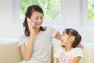 ソファーでスマートフォンを操作する母子の写真素材 [FYI01480818]