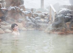 雪と露天風呂に入る20代女性の写真素材 [FYI01480830]