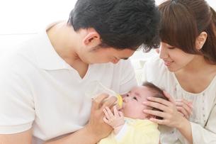 赤ちゃんにミルクをあげる両親の写真素材 [FYI01480872]