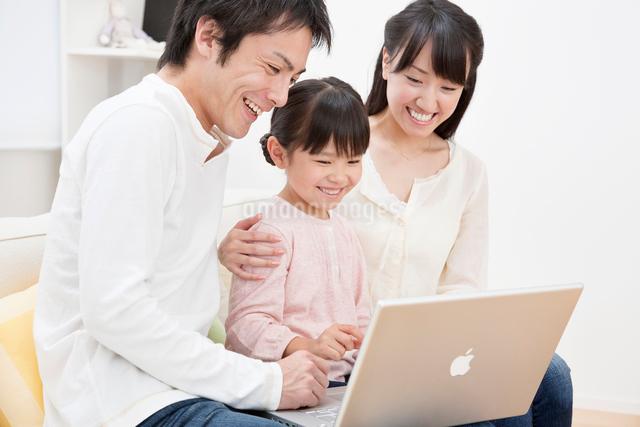 ソファーでパソコンを操作する家族の写真素材 [FYI01480882]