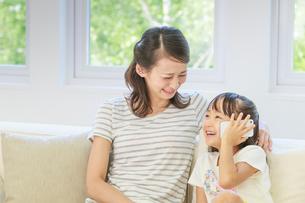 ソファーでスマートフォンを操作する母子の写真素材 [FYI01480886]