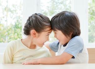 おでことおでこをくっつける女の子と男の子の姉弟の写真素材 [FYI01480891]