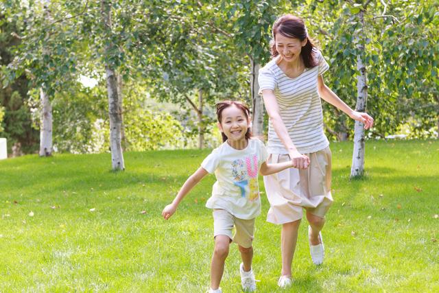 新緑の中、手をつないで走る母子の写真素材 [FYI01480921]