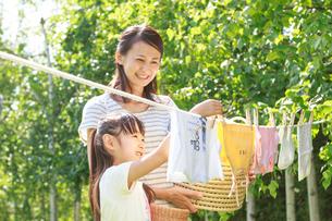 新緑の中、洗濯物を干す母子の写真素材 [FYI01480926]