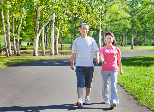 緑の中でウォーキングするトレーニングウェアの60代シニア夫婦の写真素材 [FYI01480930]