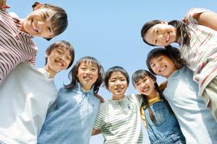 青空の下 肩を組む7人の小学生の男の子と女の子の写真素材 [FYI01480937]