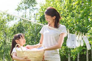 新緑の中、洗濯物を干す母子の写真素材 [FYI01480958]