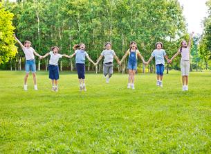 緑の中で手をつなぎジャンプする7人の小学生の男の子と女の子の写真素材 [FYI01481038]