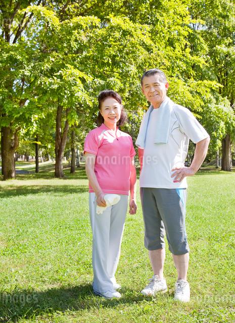 緑の中で佇むトレーニングウェアの60代シニア夫婦の写真素材 [FYI01481041]