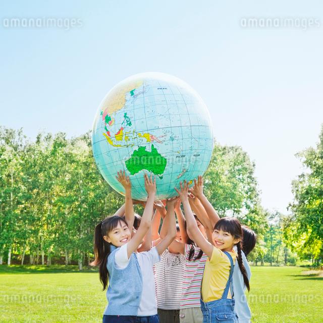 緑の中 地球儀を持ち上げる小学生の男の子と女の子の写真素材 [FYI01481054]