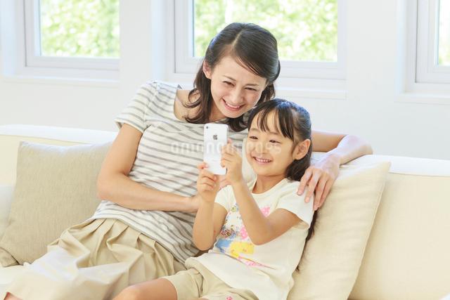 ソファーでスマートフォンを操作する母子の写真素材 [FYI01481117]
