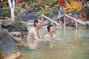 露天風呂に入る60代の夫婦と紅葉の写真素材 [FYI01481118]