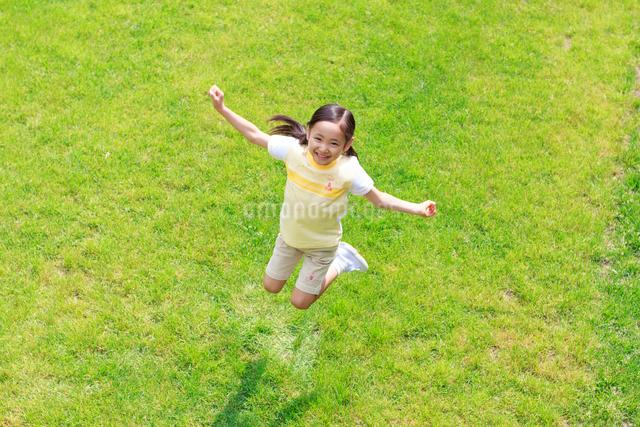 新緑の中ジャンプする6歳の女の子の写真素材 [FYI01481264]