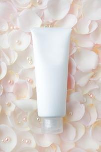 敷き詰められたバラの花びらの上の化粧品のチューブの写真素材 [FYI01481274]