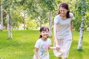 新緑の中、手をつないで走る母子の写真素材 [FYI01481294]