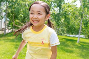 新緑の中を走る6歳の女の子の写真素材 [FYI01481307]