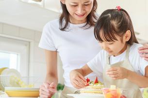 キッチンで料理をする母子の写真素材 [FYI01481336]