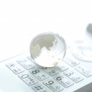 白い携帯電話に置かれたビー玉の地球儀の写真素材 [FYI01484448]