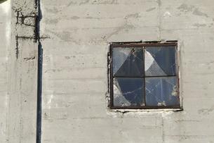 コンクリート製の建築物のひびの入ったガラス窓の写真素材 [FYI01489472]