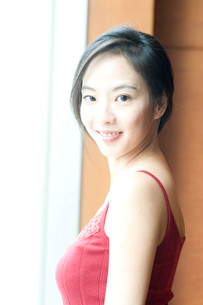 赤いキャミソールを着て振り向く女性の写真素材 [FYI01489617]