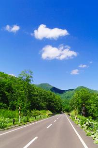山岳地帯の道路と雲浮かぶ青空の写真素材 [FYI01489839]