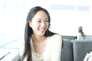 横向きで笑いかける長い黒髪の女性の写真素材 [FYI01490214]
