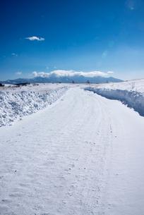 霧ヶ峰高原雪原と八ヶ岳連峰に延びる雪の道の写真素材 [FYI01492025]
