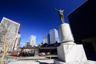 東京駅丸の内口広場の銅像と高層ビル群の写真素材 [FYI01495960]
