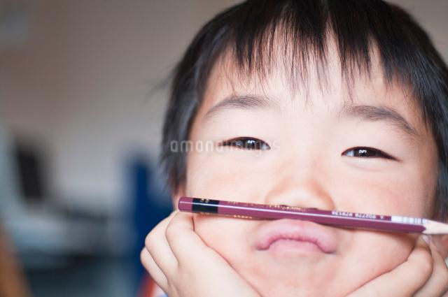 鉛筆を上唇に乗せた男の子の写真素材 [FYI01498478]