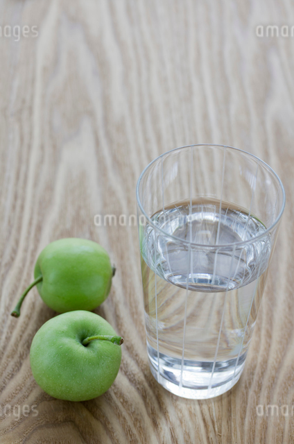 グラスに入ったミネラルウォーターとミニ青りんごの写真素材 [FYI01498918]