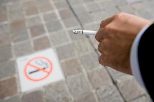 禁煙マークとタバコを持ったビジネスマンの手元の写真素材 [FYI01499667]
