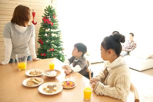 ツリーのあるリビングダイニングでおやつを食べる家族の写真素材 [FYI01501034]