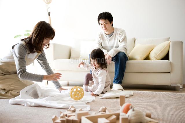 洗濯物をたたむ母親と遊ぶ子供の写真素材 [FYI01501084]