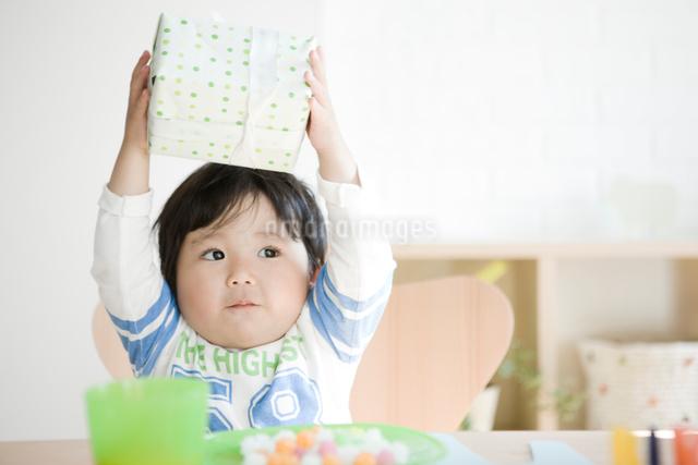 プレゼントを上に上げる子供の写真素材 [FYI01501087]
