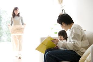 ソファで本を読む子供と父親の写真素材 [FYI01501144]