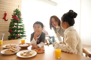 ツリーのあるリビングダイニングでおやつを食べる家族の写真素材 [FYI01501284]