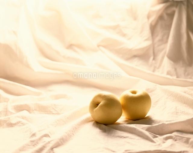 黄色いリンゴとシーツの写真素材 [FYI01501458]