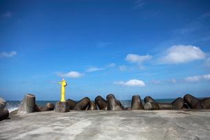 青い空の下の堤防のテトラポットと黄色い灯標の写真素材 [FYI01501642]