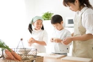 料理の手伝いをする子供と母親の写真素材 [FYI01501725]