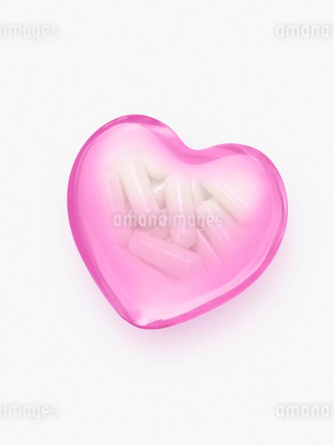 ピンクのハートとカプセルの薬の写真素材 [FYI01501756]