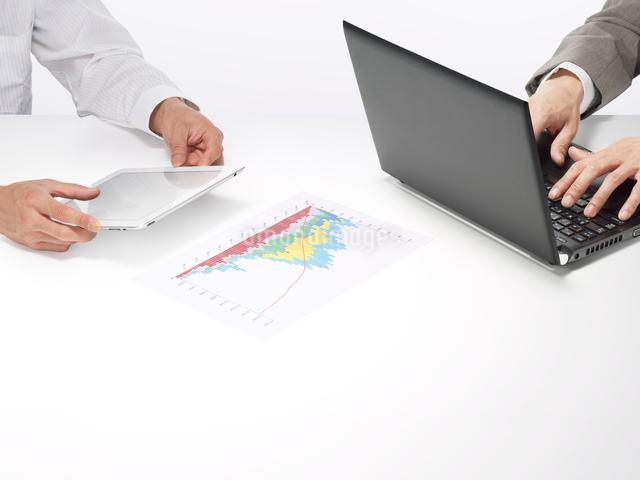 スマートデバイスとパソコンを使うビジネスマンの写真素材 [FYI01501786]