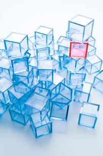 積み上げた青アクリルキューブ群と赤アクリルキューブの写真素材 [FYI01501844]