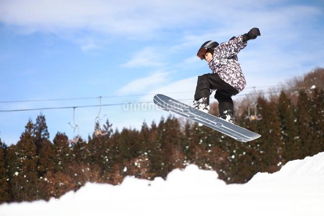 スノーボードでジャンプする少年の写真素材 [FYI01501879]