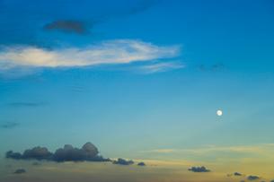 夕日に染まる雲と月の写真素材 [FYI01501899]