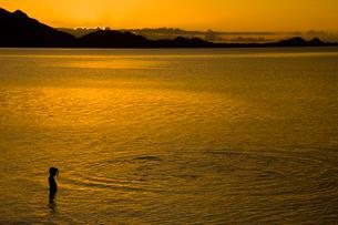 夕暮れに水紋を見つめる子供の写真素材 [FYI01501979]