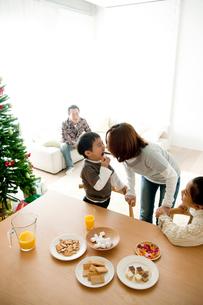 ツリーのあるリビングダイニングでおやつを食べる家族の写真素材 [FYI01502041]