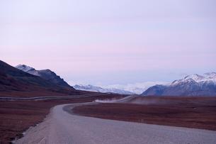 朝焼けのアラスカの大地を走るトラックの写真素材 [FYI01502258]