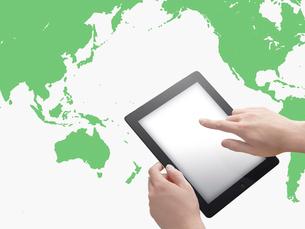 スマートデバイスを操作する手と世界地図の写真素材 [FYI01502363]