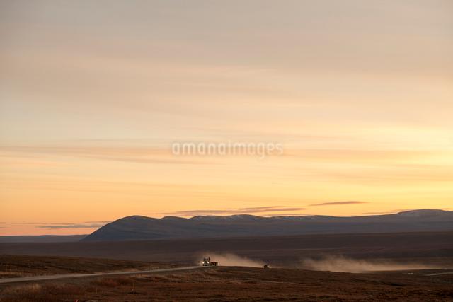 朝焼けのアラスカの大地を走るトラックの写真素材 [FYI01502776]